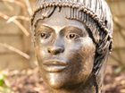 A highly decorated African female head inspired by the wonderful photograph book 'The People of Kau' by Leni Riefenstahl.They belong to the Nuba Tribe of the Sudan, a wild and passionate people whose primitive life style is fast disappearing. Suitable for a garden setting and cast in frost proof resin. 